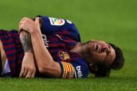 Lionel Messi kesakitan saat mengalami patah lengan dalam laga melawan Sevilla, Minggu (21/10).
