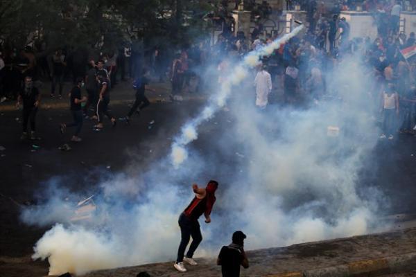 Demonstran Baghdad berhadapan dengan tembakan gas air mata dari pihak keamanan (foto: Israelnational)