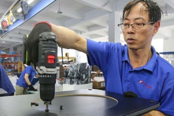 Seorang pekerja membuat meja untuk diekspor ke AS, Prancis, Jerman dan negara-negara lain, di sebuah pabrik di Nantong di China. (Foto: AFP)