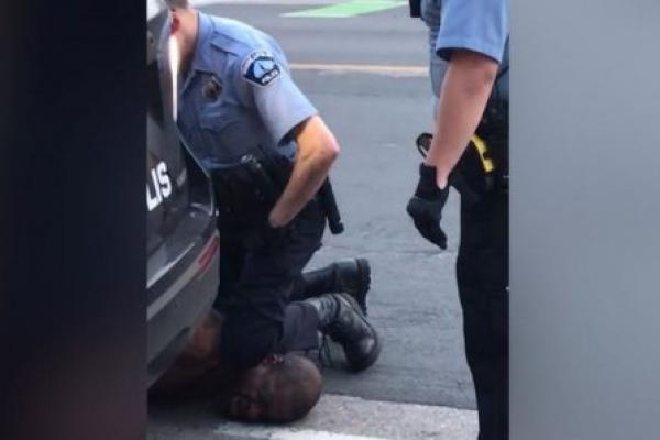 Seorang polisi saat membengkuk  George Floyd yang menyebabkan kematian