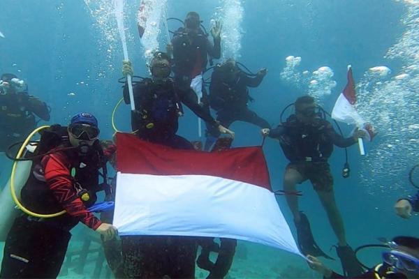 Para personel Polda Aceh mengibarkan bendera merah putih di dalam laut titik nol kilometer, Jumat (14/8/2020).