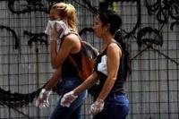 Dua wanita menggunakan plastik sebagai sarung tangan untuk mencegah penularan virus Corona di Caracas, Venezuela, 14 Maret 2020.(foto: tempo.co/ REUTERS)