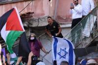 Pemukim Israel di lingkungan Palestina Sheikh Jarrah bereaksi ketika aktivis Palestina dan Israel meneriakkan slogan di depan rumah mereka selama demonstrasi menentang pengusiran keluarga Palestina dari rumah mereka di Yerusalem timur yang dicaplok Israel pada 16 April 2021. [EMMANUEL DUNAND / AFP