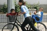 Ilustrasi. Seorang ibu membonceng sepeda  dua anaknya (foto: tionghoa.info)