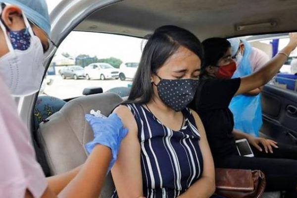 Seorang wanita menerima dosis vaksin COVID-19 di kios vaksinasi drive-in di Ahmedabad, India, 27 Mei 2021. (Foto: REUTERS/Amit Dave)