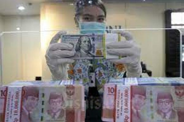Seorang karyawati menunjukan Uang Rupiah dan Dollar AS di salah satu kantor cabang Bank BNI di Jakarta, Kamis (3/9/2020). (foto: bisnis.com)