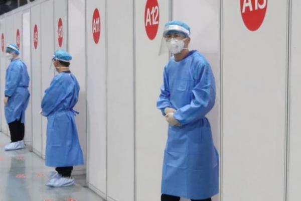 Anggota staf menunggu di luar bilik tempat orang menerima vaksin COVID-19 di pusat vaksinasi, selama kunjungan yang diselenggarakan pemerintah, di Beijing, Cina, 15 April 2021. (Foto file: REUTERS/Thomas Peter)